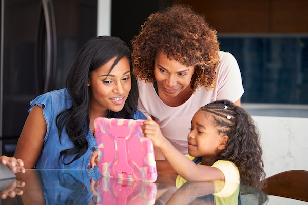 Grandmother With Mother Helping Granddaughter To Do Homework On Digital Tablet