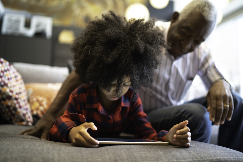 Grandfather and granddaughter playing with digital tablet